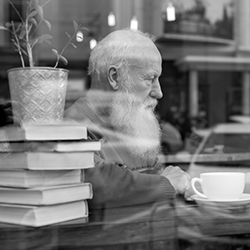 man with coffee and books