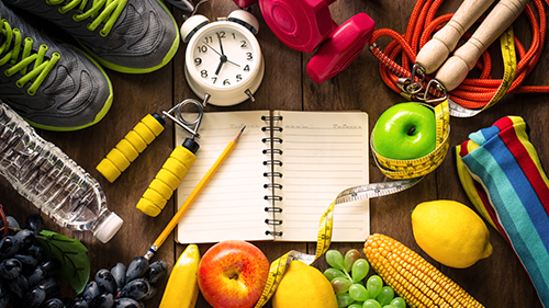 Various equipment and items used to live a healthy lifestyle, such as fruits, stopwatch, notebook, weights, jump rope, running shoes etc.